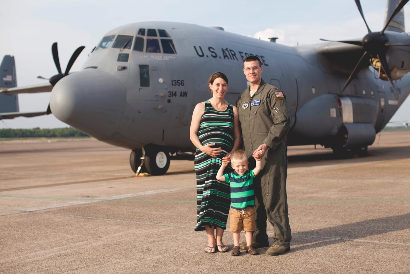 Maj. Jacob Fuchs (Class of 2002) pictured in front of a C-130 aircraft with his wife Linsey and his son, Elijah.