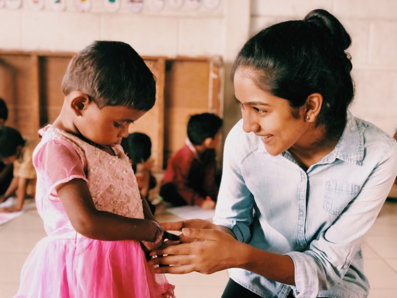 Hridika Shah holds the hand of a child in a makeshift classroom in India. Learn more about Hridika, her sister, and their selfless service in this edition of Our Schools.