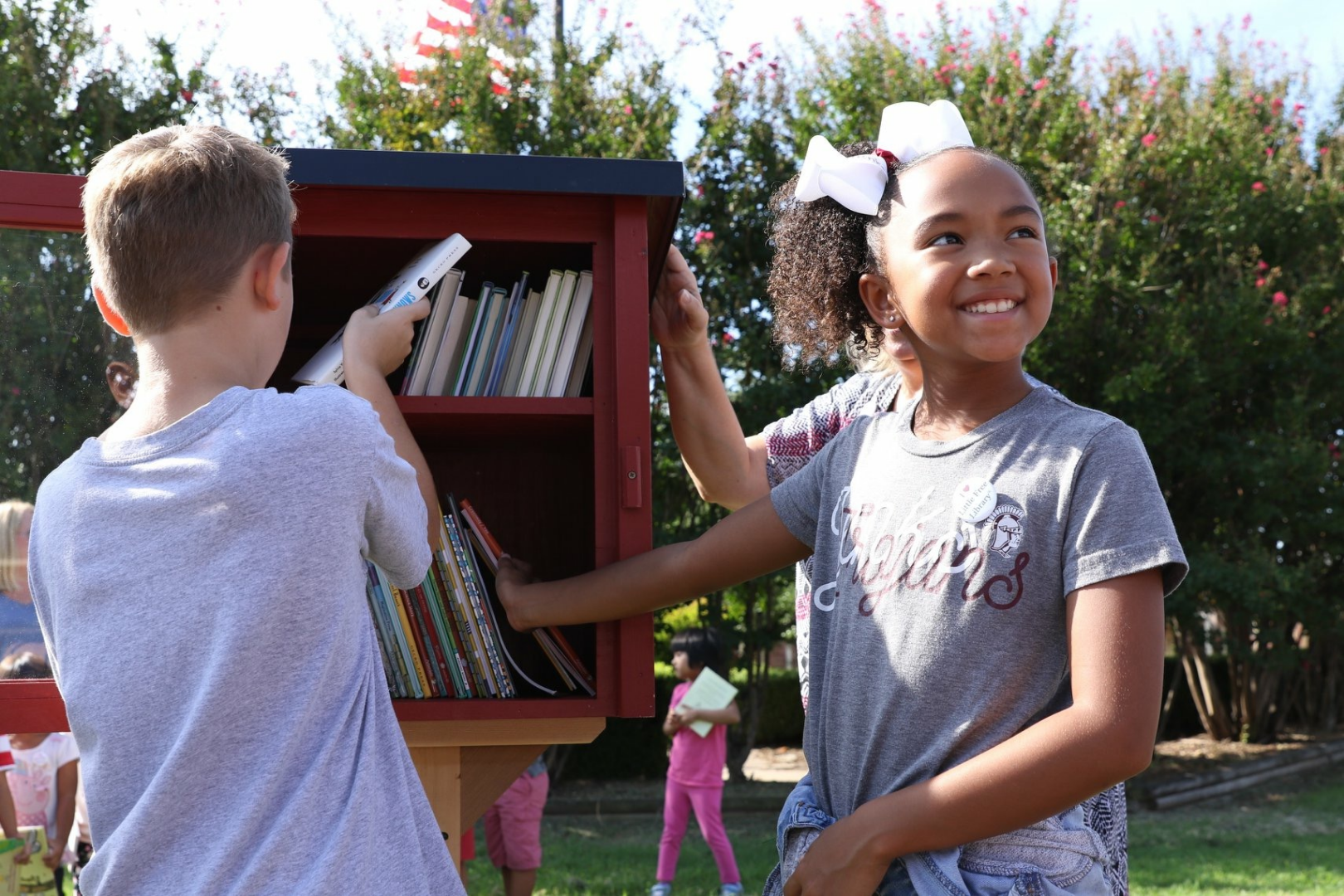 Students place books in the Little Free Library at East Elementary.
